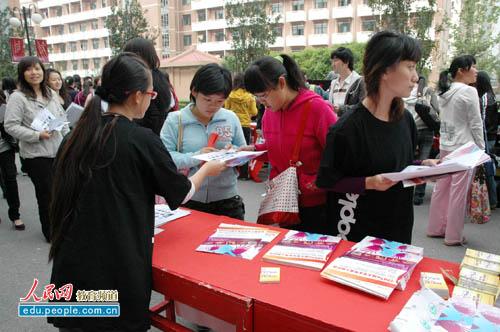 中国 石油大学/戏曲学院学生认真阅读大学生评选活动宣传单